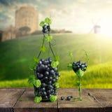 瓶酒和玻璃由葡萄叶子制成和一束葡萄在木背景 免版税库存图片