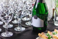 瓶酒和空的玻璃在桌上设置了 库存图片