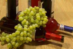 瓶酒和葡萄。 库存图片