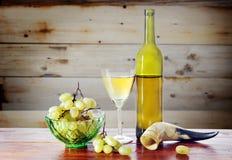 瓶酒和葡萄反对木表面 库存图片