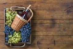 瓶酒和葡萄在木箱的在木桌上 图库摄影