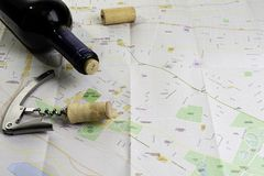 瓶酒和黄柏在地图路线计划的 拔塞螺旋开启者 库存照片