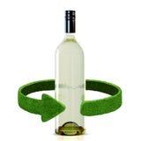 瓶酒和绿色箭头从草 回收在白色的概念隔离 免版税库存照片