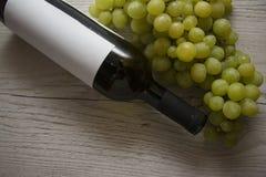 瓶酒和绿色葡萄 库存照片