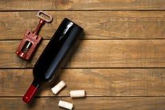 瓶酒拔塞螺旋和拔塞螺旋在木背景 与拷贝空间的顶视图 免版税库存图片