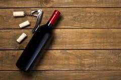 瓶酒拔塞螺旋和拔塞螺旋在木背景 与拷贝空间的顶视图 免版税库存照片