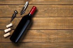 瓶酒拔塞螺旋和拔塞螺旋在木背景 与拷贝空间的顶视图 库存图片