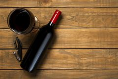 瓶酒杯和拔塞螺旋在木背景 与拷贝空间的顶视图 免版税库存图片