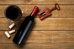 瓶酒杯拔塞螺旋和拔塞螺旋在木背景 与拷贝空间的顶视图 库存图片