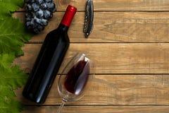 瓶酒杯葡萄和拔塞螺旋在木背景 与拷贝空间的顶视图 免版税图库摄影