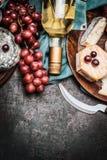 瓶酒用美好的乳酪和葡萄在黑暗的土气背景,顶视图 免版税库存照片