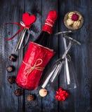 瓶香槟、巧克力、玻璃和心脏与丝带在深蓝木背景 免版税库存图片