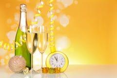 瓶香槟、玻璃、圣诞节玩具、礼物和时钟,在明亮的黄色 库存照片