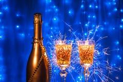 瓶香槟和玻璃与在新年和xmas在蓝色背景 免版税库存图片