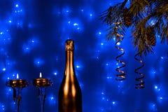 瓶香槟和蜡烛与圣诞树在蓝色背景分支 图库摄影