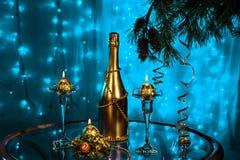 瓶香槟和蜡烛与圣诞树在蓝色背景分支 免版税库存图片