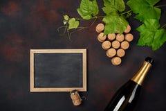 瓶香槟,葡萄在生锈的背景的束与叶子的黄柏和黑板 库存照片