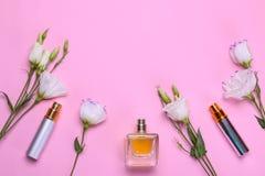 瓶香水和美丽的花南北美洲香草在明亮的桃红色背景 妇女` s辅助部件 顶视图 免版税库存照片