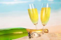 瓶,两块玻璃用香槟,在沙子的时钟反对海 图库摄影