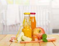 瓶从不同的类型苹果的汁液在背景厨房 库存图片