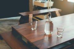 瓶水和玻璃在一张木桌安置在咖啡店,等待顾客点食物 免版税库存图片
