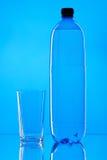 瓶水和玻璃在蓝色背景 免版税库存图片