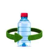 瓶水和绿色箭头从草 回收在白色的概念隔离 图库摄影
