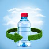瓶水和绿色箭头从草 回收概念 免版税库存图片