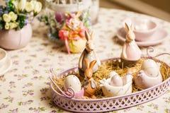瓷复活节bunnys或兔子用鸡蛋在桌上 库存图片