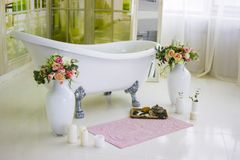 瓷独立浴在被设计的白色卫生间里 白色豪华浴,花花束在一个大花瓶的 静物画或 库存图片