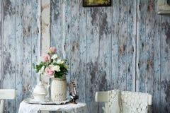 瓷茶壶和杯子在一张桌上与一个花瓶有人为的 免版税图库摄影