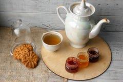 瓷茶壶和茶杯用绿茶在木背景 免版税库存图片