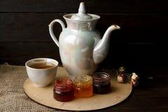 瓷茶壶和茶杯用绿茶 在一张木桌上的被按的玫瑰 三个小瓶子自创莓果在向求爱阻塞 免版税库存图片