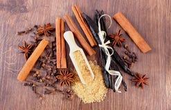 甘蔗、香草、肉桂条、八角和丁香在木表面板条 免版税库存图片