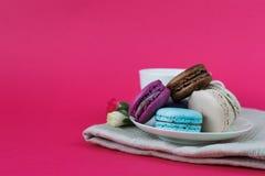 甜五颜六色的蛋白杏仁饼干 正面图 在茶碟的法国macarons 甜的bisquits Delicios甜点 流行粉红背景 表c 图库摄影