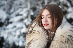 甜俏丽的女孩在冬天公园 免版税库存图片