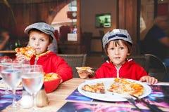 甜可爱的孩子,两个男孩,吃薄饼在餐馆 免版税库存图片