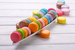 甜和五颜六色的法国蛋白杏仁饼干排行了以在白色背景的一条鳄鱼的形式 免版税库存照片