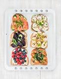 甜和美味早餐敬酒分类 三明治用果子,菜,鸡蛋,在白色烘烤的熏制鲑鱼 免版税库存图片