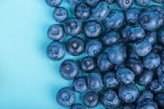 甜和水多的越桔 在明亮的蓝色背景,顶视图的蓝莓 健康和鲜美莓果,特写镜头 美满的果子石榴红色种子夏天 免版税库存照片