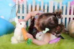 甜在复活节的小孩女孩哺养的兔宝宝 免版税库存图片
