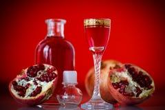 甜在蒸馏瓶的石榴酒精甘露酒有玻璃的 免版税库存图片