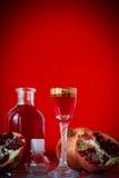 甜在蒸馏瓶的石榴酒精甘露酒有玻璃的 免版税库存照片