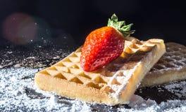 甜多士胡扯用与叶子的草莓在上面和过滤在阳光特写镜头的倾吐的糖粉末 免版税库存照片