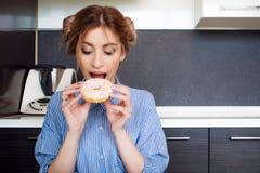 甜多福饼的美好的白肤金发的叮咬 不健康的食物,甜点 免版税库存照片