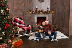 甜夫妇坐在装饰的fireplac前面的一个地毯 库存照片