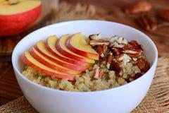 甜奎奴亚藜粥用果子和坚果 素食主义者奎奴亚藜粥用新鲜的苹果和胡桃在一个白色碗 土气样式 免版税库存照片