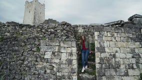甜女孩下来一个古老堡垒的石步以一座高塔为背景 股票视频
