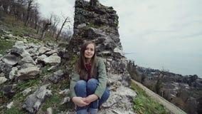 甜女孩由古老堡垒墙壁的遗骸坐在小山由海并且周道地看,然后她 股票视频