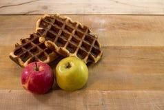 甜奶蛋烘饼和苹果在书桌上 库存照片